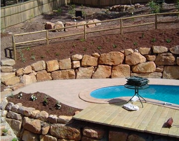 SWIMMING POOL WITH ROCK RETAINING WALL